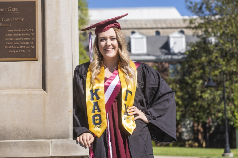 An EKU student in cap and gown leans on a pillar