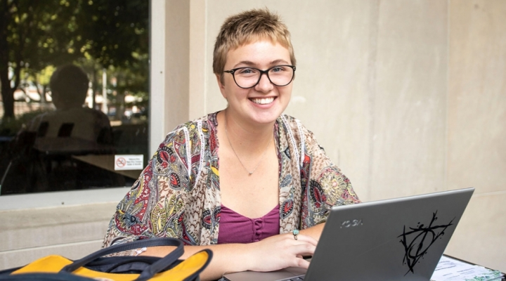 Woman sitting at outside table with laptop