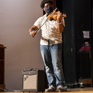 A male EKU student plays a violin solo on stage