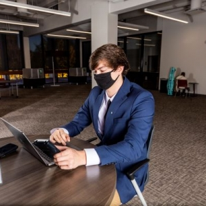 A male EKU student in suit and tie works on a laptop