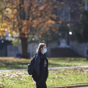 A student in a protective mask walks through campus